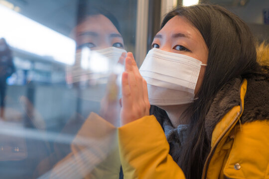lifestyle portrait of young beautiful and thoughtful Asian Chinese woman in face mask as protection vs covid19 looking through window during train trip