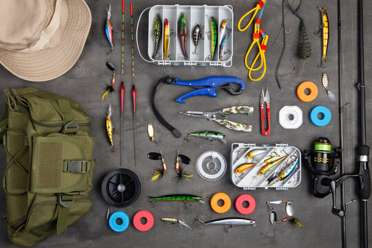 Fishing tackle - fishing spinning rod, hooks and lures on gray background. Active hobby recreation concept.
