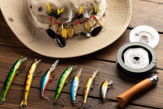 Fishing tackle - fishing spinning rod, hooks and lures on wooden background. Active hobby recreation concept.