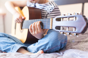 Fototapeta The child plays an acoustic guitar. Learning to play a musical instrument online