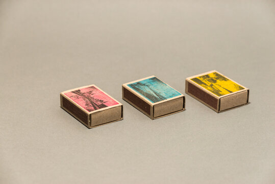 Three closed matchboxes (pink, blue, yellow).