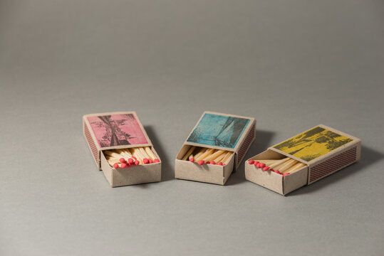 Three opened matchboxes with red matches.