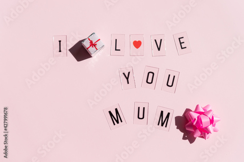 Happy mother's day concept. Top view of message LOVE MUM text on pink pastel background.lovely greeting card. Black letters , red heart.Copy space