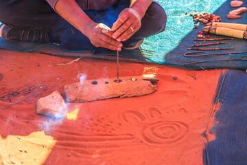 Fototapeta Unrecognizable indigenous Australians craftsman making wooden crafts decorated with fire burns. Northern Territory, Australia obraz