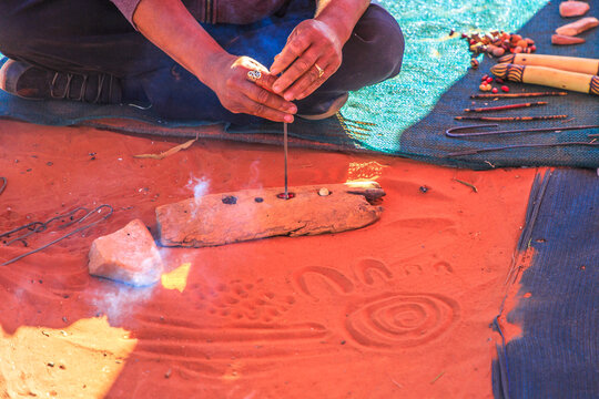 Unrecognizable indigenous Australians craftsman making wooden crafts decorated with fire burns. Northern Territory, Australia