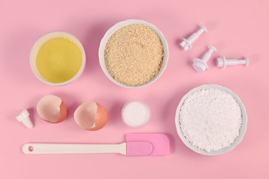 Ingredients for making homemade French Macarons sweets including powdered sugar, ground almonds, egg white, salt and baking tools on pink background