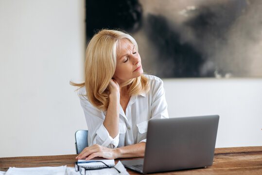 Successful relaxed tired middle aged caucasian blonde woman, business lady or lawyer, wearing white shirt, sitting at a table, taking break, closes eyes, overworked, exhausted
