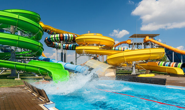 water park, bright multi-colored slides with a pool, a water park on a summer day