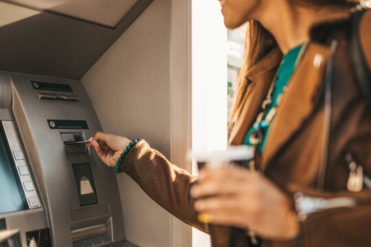 Young woman withdraws money from ATM machine.