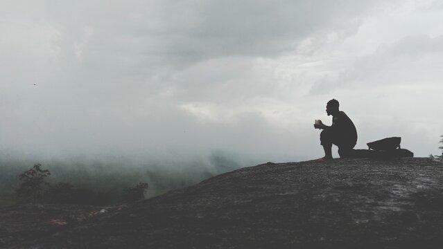 Man Standing On Rock Looking Away Against Sky