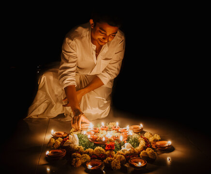 Man Standing By Illuminated Candles On Table