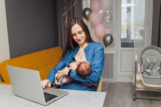 Beautiful young mother working with laptop computer and breastfeeding, holding and nursing her newborn baby at home. Mom - business woman feeding newborn.