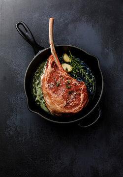 Raw fresh meat Tomahawk Steak in Cast iron frying pan on dark background