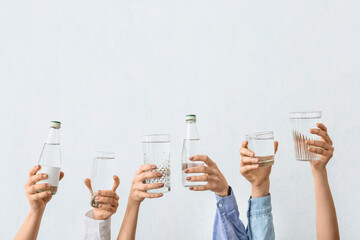 Female hands with bottles and glasses of water on grey background