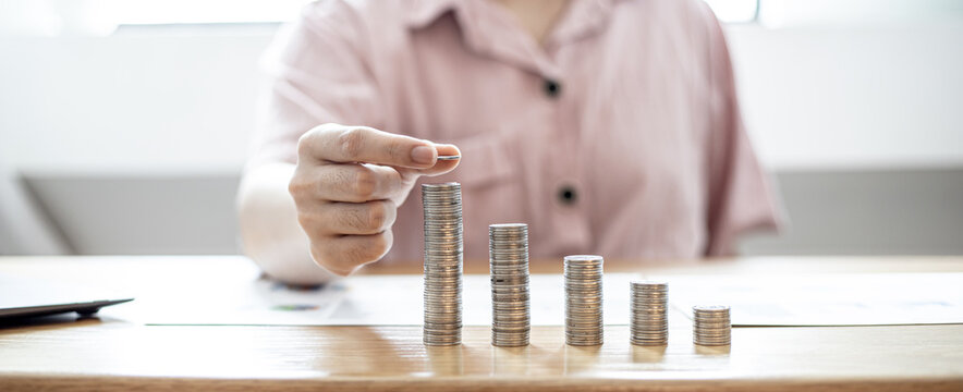 A woman is holding coins in five rows from low to high, she is accounting for income and expenses and dividing her savings. Concept of saving money and investing it to grow money.