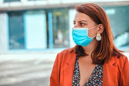 Business lady with foxy hairwearing protection face mask against coronavirus MERS-Cov, Novel coronavirus 2019-nCoV. Concept of coronavirus quarantine and pandemic