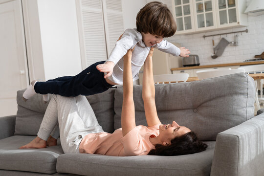 Happy loving mother with cute son wear pajamas imitate plane lying on couch in morning on weekend. Caring mom have fun with happy laughing preschool boy, enjoy family time at home at covid lockdown