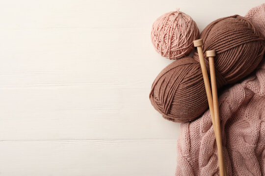 Woolen yarns, knitting needles and sweater on white wooden background, flat lay. Space for text