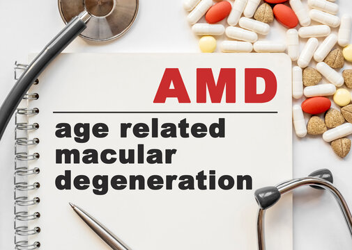 Page in notebook with AMD age related macular degeneration on white background with stethoscope and group of pill. Medical concept. Term and abbreviation