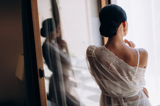 morning of the bride, getting ready, the bride in a robe stands on the balcony in front of a large window