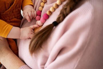 Fototapeta woman carrying her baby daughter. Baby girl touching teething beads