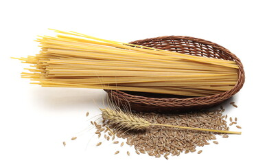 Raw spaghetti in woven wicker basket with wheat ear and spelt grains isolated on white background