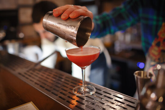 Bartender is preparing a pink cocktail in a shaker with grapefruit. A man's hand pours bloody Mary into a large glass. Red-pink alcoholic drink in a large glass on the table