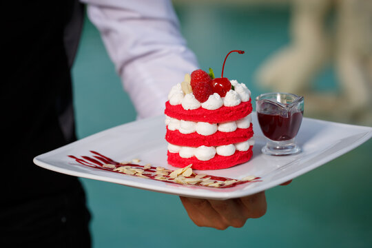 Delicious fresh millefeuille dessert on a white plate decorated with raspberries and cherry berries. Dessert on a large white plate in the hands of a waiter on the background of the pool. Without face