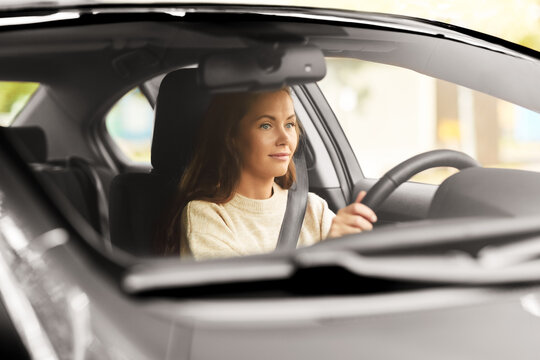 safety and people concept - young woman or female driver driving car in city