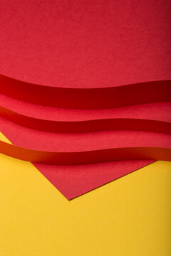 Abstract minimal paper background. Three red cut out paper stripes on red and yellow paper background.