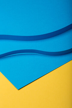 Abstract minimal paper background. Two blue curvy cut out paper stripes on blue and yellow paper background.