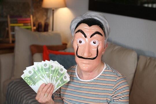 Senior lady wearing mask and holding euros