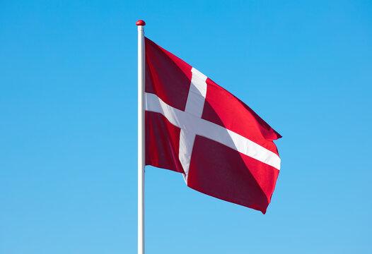 flagpole with danish flag against blue sky