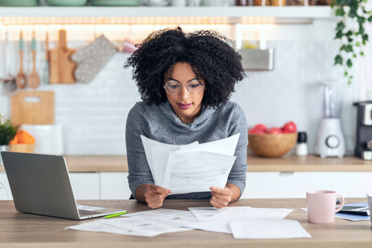 Shot of pretty afro business woman working with computer while consulting some invoices and documents in the kitchen at home.