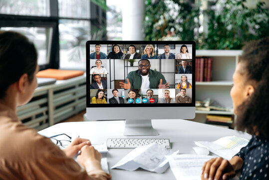 Virtual communication, video call. View over the shoulders of two women to a computer screen with successful multiracial business team gathered in a video conference to discuss working issues,strategy