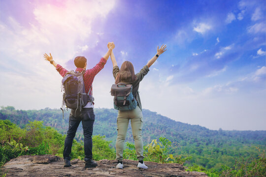 Couples hiker standing and open arms on mountain peak celebrate their freedom vacation.