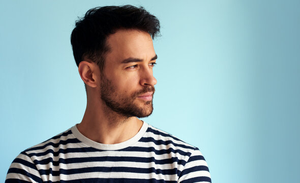 Closeup portrait of handsome young man looking at one side, posing for advertisement, isolated on light blue background. Male has pensive expression, posing against white blue wall.