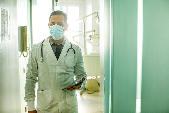 Dottore con i capelli neri in camice bianco e mascherina chirurgica, cammina frettolosamente  con il tablet in mano   lungo la corsia di un ospedale