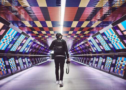 person walking in a colourful subway