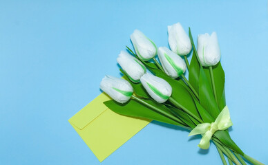 White tulips bouquet with yellow envelope on the blue background. Minimal spring flower concept. Easter, Woman day, mother day, birthday, wedding greeting card. Copyspace for text, flatly, banner. Wall mural