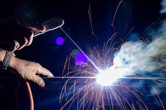 Iron welding close-up, sparks do not wear gloves. Welding sparks and fumes It can be dangerous to health.