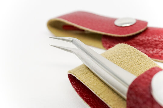 Close-up shot of a curved eyelash extension tweezers in a red leather case with magnetic button on top of a white background.