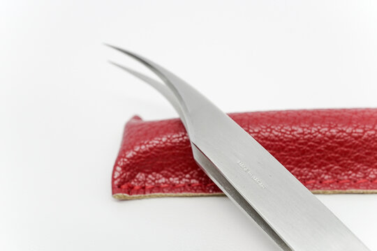 Close-up shot of a curvy eyelash extension tweezers in a red leather case with magnetic button on top of a white background.