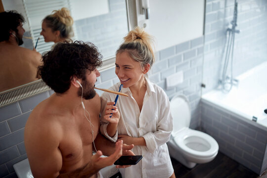 young adult couple brushing teeth together, looking each other, smiling. Valentine