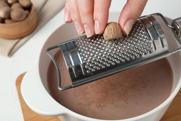 Fototapeta Woman grating nutmeg into cacao at table, closeup obraz