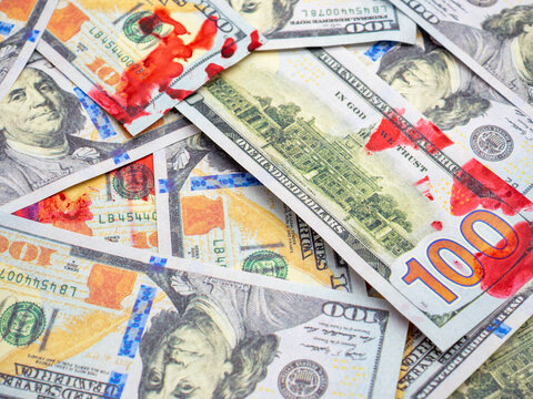 Closeup shot of dollar bills with red blood spots on them