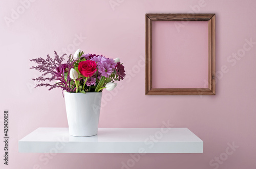 Room interior with blank picture frame and flowers