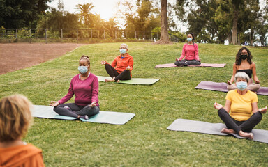Multiracial people doing yoga class outdoor with social distance while wearing safety mask - Coronavirus outbreak, healthy lifestyle and sport concept