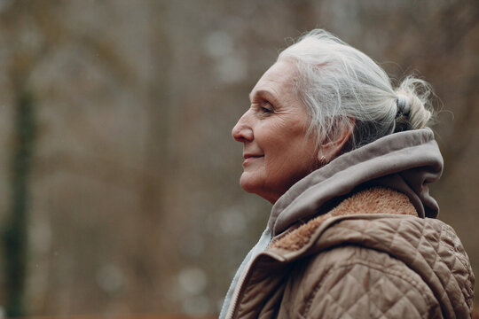 Portrait profile of smiling gray haired elderly woman outdoor