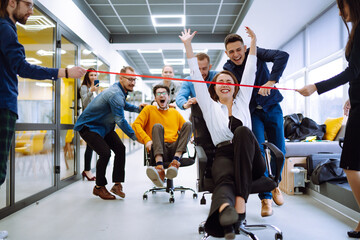 Fototapeta Friendly work team  ride chairs in office room cheerfully excited diverse employees laugh while enjoying fun work break activities, creative friendly workers play a game together.